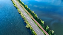 Aerial drone view of motorway road and cycling path on polder dam, cars traffic from above, North Holland, Netherlands