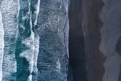 Aerial drone view of ocean waves washing black basaltic sand beach, Iceland