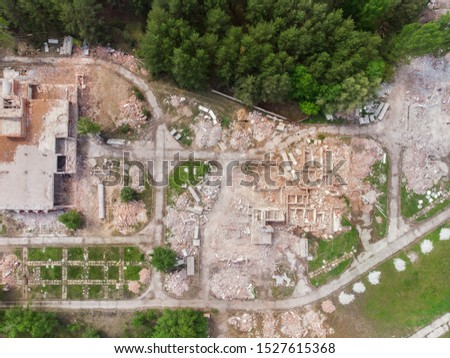 Aerial drone view of old demolished industrial building. Pile of concrete and brick rubbish, debris, rubble and waste of destruction ruins of abandoned actory or plant. Earthquake city landscape
