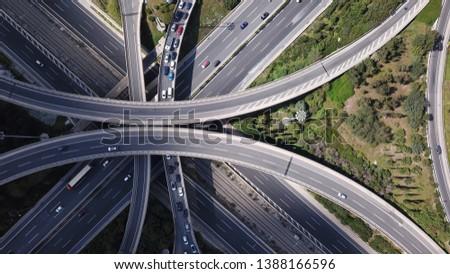 Aerial drone view of popular highway multilevel junction road, passing through National motorway in traffic jam #1388166596