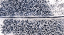 Aerial drone view of road in idyllic winter landscape. Street running through the nature from a birds eye view.
