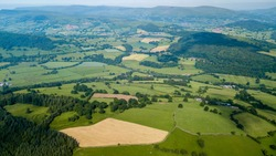 Aerial drone view of rural Wales showing farmed fields and green rolling hills