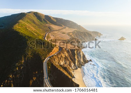 Aerial drone view of the Big Sur coastline in California. Beautiful golden light hitting the side of the cliffs at sunset along the coastal road.  Stock photo ©