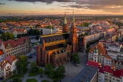 Aerial drone view of the Cathedral of St. Peter and Paul the Apostles and old town buildings before sunset. The sun's rays beautifully highlight the urban architecture in Legnica, Poland