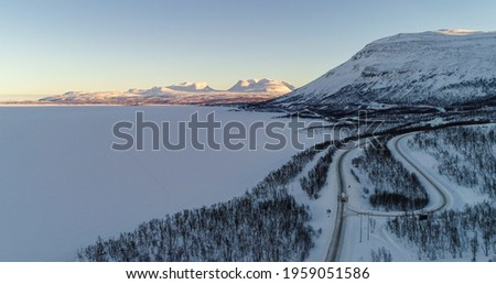 Aerial drone view of the gate of lapponia, the Lapporten mountains, Tornetrask lake, Abisko sunny winter evening, in Lappland, Swede Stock foto ©