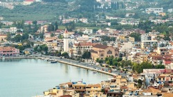 Aerial drone view of the Ionian Sea port of Zakynthos, Greece. Port with moored boats, embankment street, buildings and greenery