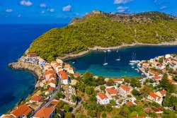 Aerial drone view video of beautiful and picturesque colorful traditional fishing village of Assos in island of Cefalonia, Ionian, Greece. Peninsula of Assos in Cephalonia (Kefalonia), Greece