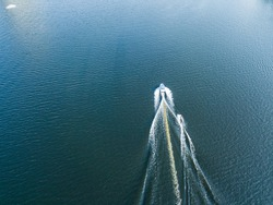 Aerial drone view. Wake surfing behind a boat on the river on a sunny summer day.