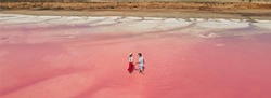Aerial epic drone image of lovely romantic couple standing in bright colorful pink water of lake with salty coast. Baner panoramic view. Concept inner tourism