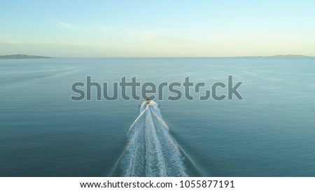 AERIAL: Fishing boat leaves a trail in the calm ocean water as it speeds towards endless horizon on a picturesque summer day. Flying behind fisherman speeding in small boat into the vast open ocean. #1055877191