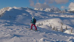 AERIAL: Fit female splitboarder hikes up a scenic mountain in picturesque Slovenia. Spectacular shot of a snowy valley as young woman hikes along a meadow during a ski touring trip in Velika Planina.