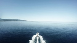 Aerial flight bird view behind fancy speedboat moving fast over quiet flat sea very beautiful day white fast ship moving straight over blue water in background showing shore island and blue sky 4k