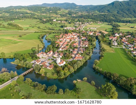 AERIAL: Flying above a beautiful small village built around the meandering river Krka. Historic buildings and lush green nature surrounds a stream meandering across the vibrant Slovenian countryside. Stock photo ©