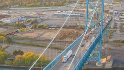 AERIAL: Flying above semi trucks transporting goods on multiple lane highway between Canada and America. Cars driving on turnpike over Ambassador Bridge, Detroit. Busy international border crossing