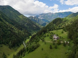 AERIAL: Flying over a small farm atop of a hill in scenic Logarska Valley in Slovenia. Picturesque drone view of a lush green gorge in Logarska Dolina on a beautiful summer day. Mountains of Slovenia.