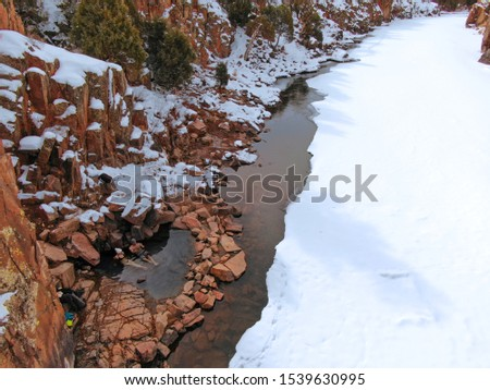 AERIAL: Flying towards two travelers taking a dip in the hot springs in snowy Colorado. Cool drone shot of a tourist couple sitting in a hot pond in the middle of the ruthless snow covered wilderness. stock photo