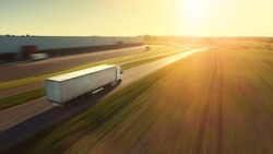 Aerial Follow Shot of White Semi Truck with Cargo Trailer Attached Moving Through Industrial Warehouse, Rural Area. Sun Shines and the Sky Are Blue. Blur motion.