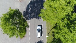 Aerial following car top-down view this grey colored station wagon is driving over two way street with green trees on both sides of street
