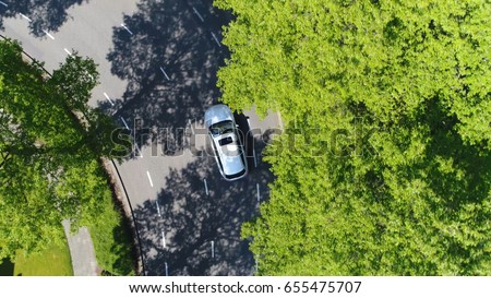 Aerial following car top-down view this grey colored station wagon is driving over two way street corner green trees on both sides of street