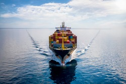 Aerial front view of a loaded container cargo vessel traveling over calm ocean