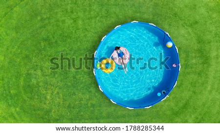 Aerial. Girl swims in a metal frame pool with inflatable toys. Frame pool stand on a green grass lawn. Top view. Copy space.