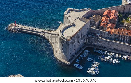 Aerial helicopter shoot of Dubrovnik old town harbor and st. John fortress.