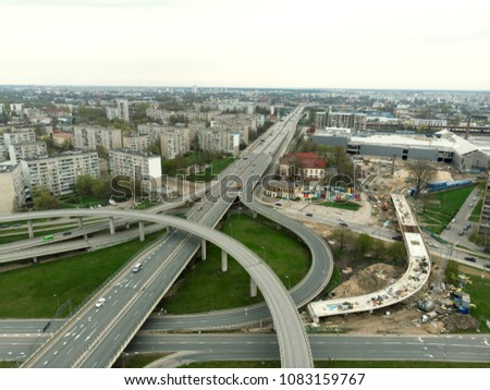 Aerial highway junction. Highway from aerial view. Urban highway and lifestyle concept. Construction of additional concrete road curve of viaduct in Riga, Latvia #1083159767