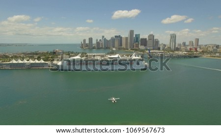 Aerial. Hydroplane  in the Miami harbor near Cruise Ship. USA. Port passenger terminal and cruise liner in harbor.  #1069567673