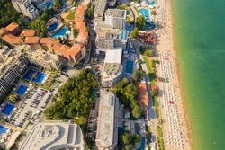 Aerial image a drone resort Golden Sands on Black Sea coast in Bulgaria. Many hotels and beaches with tourists, sunbeds and umbrellas. Sea travel destination. Travel and vacation concept