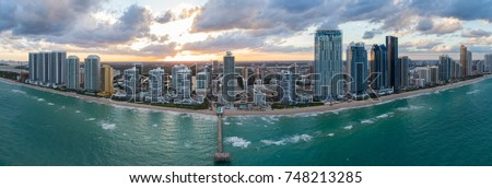 Aerial image of a beautiful sunset behind Sunny Isles Beach fishing pier and beachfront condos and hotels