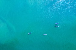 Aerial image of four Paddle boarders with sunlight reflecting off blue green water