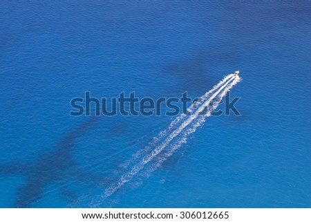 Aerial image of motorboat floating in a turquoise blue sea water. The boat is moving diagonally through the frame of the photo.