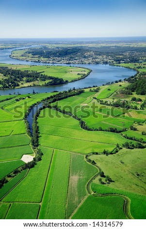Aerial landscape shot of sugarcane farms and river