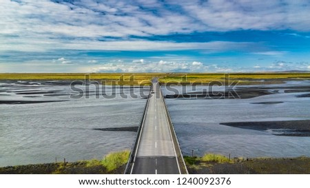 Aerial landscape view of a bridge with a car crossing and riverbed in Iceland