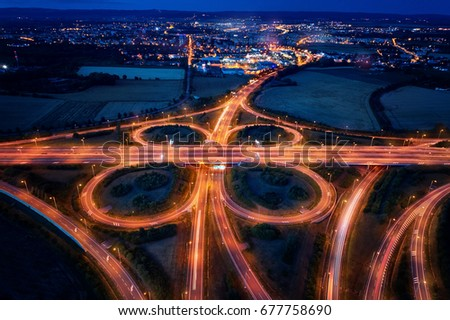 Aerial, late evening view on highway junction in the shape of butterfly wings, illuminated by lamps and light trails, illuminated city in dark blue background. Long exposure photo.