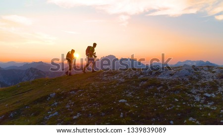 AERIAL, LENS FLARE: Carefree young trekkers on an active summer vacation hiking uphill on a picturesque summer morning. Tourist couple exploring the stunning Julian Alps at sunrise. Fun recreation. #1339839089