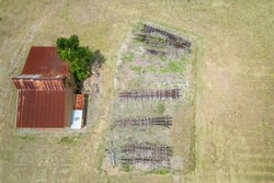 Aerial looking down onto old discarded train tracks stacked in front of a vintage rusted shed that was once part of Finch Hatton mill, Mackay, Queensland