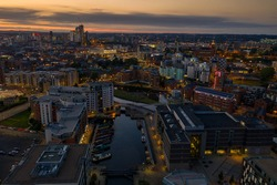 Aerial night time photo taken at sunset of  the area in Leeds known as The Leeds Dock showing the whole of the West Yorkshire city with the sun setting in the background