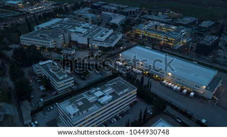 Aerial night view of an industrial area of a large Italian city with warehouses, warehouses, offices and buildings. Among the asphalt roads beyond the cars, vans and trucks there are trees.