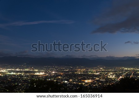 Aerial night view of Kofu city in Yamanashi prefecture, Japan. Mt.Fuji is in the middle of the photograph.