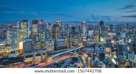 Aerial night view of Osaka city - Asia business city concept image, panoramic modern metropolis bird's eye view at evening, shot in Umeda Sky Building observatory, Osaka, Japan.