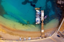 Aerial of a beautiful beach with boat peer. A wharf shot from a drone in Greece on Corfu island. Boats and a vivid torquoise mediterranean sea