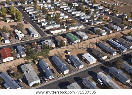Aerial of aging mobile homes in bright desert sun. - stock photo