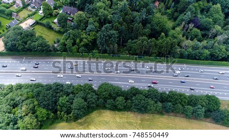 Aerial of busy highway showing tree lines and busy highway traffic