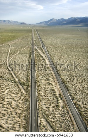 Aerial of desolate scenic highway through rural desert landscape of California, USA.