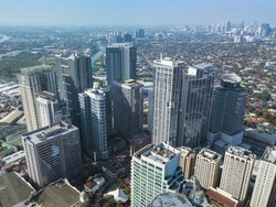 Aerial of Eastwood City skyline and distant BGC and Ortigas further ahead.