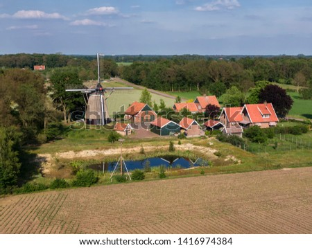 aerial of farmland scene with dutch wind mill and stork breeding on nest pole #1416974384