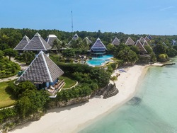 Aerial of resort bungalows and a pool, atop a short cliff and beside a white sand beach and tropical waters during a clear day.