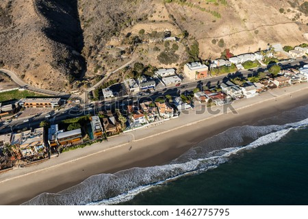 Aerial of shoreline homes and buildings north of Los Angeles and Santa Monica on Highway 1 in Malibu, California.