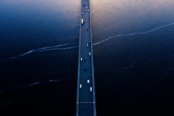 Aerial of Tasman bridge over wide flowing Derwent river in Tasmania Australia, with traffic, cars and trucks, crossing at sunset.